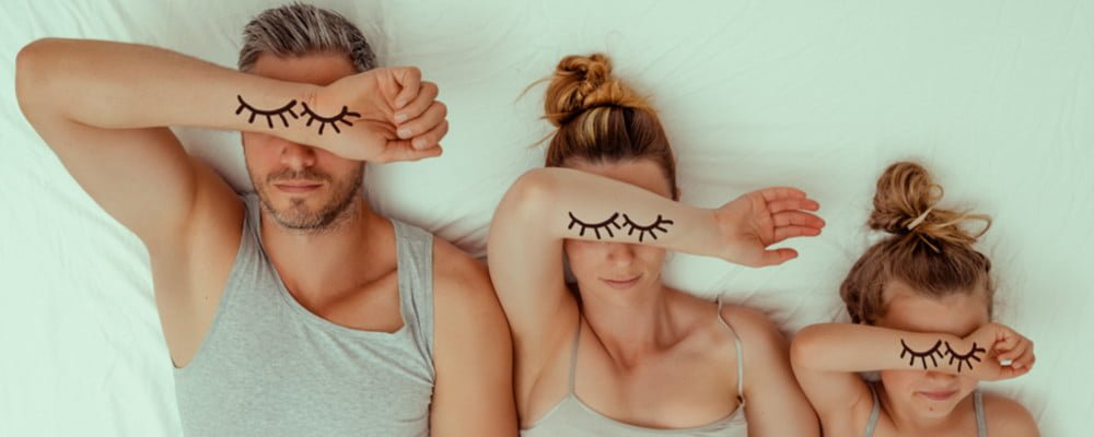 family in bed with eye lashes on forearm and over their eyes for Sleep awareness week