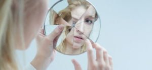 woman looking into broken mirrow representing schizophrenia. Vitamin deficiency